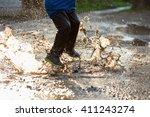 little boy splashing in a mud... | Shutterstock . vector #411243274