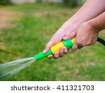women hand watering the lawn in ... | Shutterstock . vector #411321703