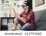 Stock photo woman touching something using virtual reality headset glasses and sitting on the couch 411791560