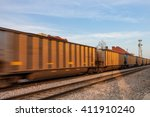 A line of identical rail cars roll through a city at sunrise - stock photo