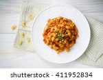 Small photo of macaroni pasta in tomato sauce with chop meat decorated with scallion on a wooden table
