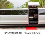 Small photo of White luxury limousine with open up door and red carpet leading to.