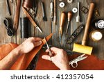 man working with leather using... | Shutterstock . vector #412357054