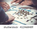 Family Hands Solving Jigsaw...
