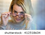 young woman trying on glasses | Shutterstock . vector #412518634