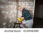 Small photo of repairwoman sutting a wooden board with a yellow handsaw and looking at the camera