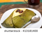 Small photo of Delicious sweet rough with raisins wrapped in achira leaf served on a white dish, quimbolito