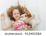 Stock photo curly little girl with her puppy jack russell terrier lying on a wooden floor 413402584