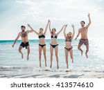 Group Of People Jumping At Beach