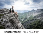 hiker sits on a mountain cliff... | Shutterstock . vector #413713549
