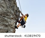 man is climbing on the rock... | Shutterstock . vector #413819470