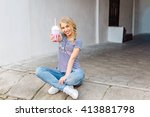 Young beautiful blonde girl walking through the city streets. In her hands a glass of drink. Smiling. Attrective girl. Sitting on the asphalt