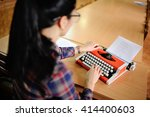 woman typing on a typewriter | Shutterstock . vector #414400603