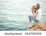 Stock photo young girl is resting with a dog on the sea 414705454
