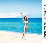 Small photo of Gorgeous, young lady with slim body and hot legs wearing white alluring swimwear walking along the seacoast with blowing silk blanket.