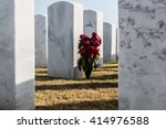 Small photo of Wilted rose bouquet and tombstones at Miramar National Cemetery in San Diego, California.