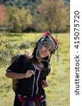 Small photo of The girl Akha's costume walking in the wild Himalayan Cherry or Thai sakura,Thailand