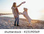 Stock photo  female with retriever dog playing on the beach during sunset or sunrise 415190569