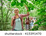 Small photo of adventure, travel, tourism, hike and people concept - group of smiling friends walking with backpacks in woods