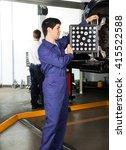 Small photo of Mechanic Adjusting Alignment Machine On Car