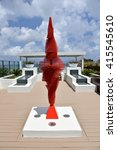 A red kinetic sculpture named Flamenco, created by the artist, Ralfonso, on an oceanfront terrace resembles a dancer when moving. - stock photo