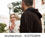 Small photo of Boring male person accosting to mature female at crowded street