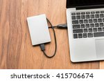 Small photo of External hard drive connect to laptop computer on wooden background