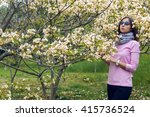 Small photo of young girl in a pink sweater and a bright scarf at the neck, smelling little white flowers tree aleurites euphorbiaceae in the spring before sunset in a Park
