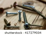 Small photo of Many scattered screws, detail of screw screwed into a wooden plank