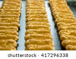 Small photo of Long rows of eclair shells. Eclairs on wide conveyor belt. Each one has perfect shape. Company's standards of production.