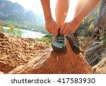 Young Woman Rock Climber Tying...