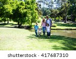 Stock photo family with their dog walking in the park near a pond 417687310