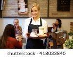 Happy blonde waitress holding...