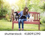 Stock photo teenage girl with dogs and cat sitting on bench in park 418091290