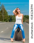 Small photo of young girl traveling across the country with a suitcase hitchhiked
