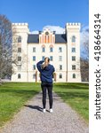 Small photo of BOGESUND, SWEDEN, APRIL 2016, young, blond, Swedish woman admiring and taking photos of Bogesund Castle on a sunny spring day.