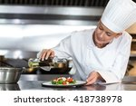 female chef pouring oil on food ... | Shutterstock . vector #418738978
