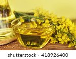 rapeseed oil with rape flowers. | Shutterstock . vector #418926400