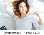 happy woman lying on the bed... | Shutterstock . vector #419084110