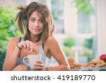 Small photo of Young messy woman have breakfast in the kitchen