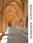 Long hall illuminated by sun at the cloister of the Monastery of Santa Maria de Santes Creus in Catalonia, Spain