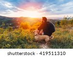 Stock photo man with beard and his small yellow dog enjoying mountain sunset and looking at the distance he is 419511310