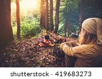 Woman traveler relaxing in forest and cooking food in kettle on fire Travel Lifestyle concept vacations outdoor picnic bivouac in forest - stock photo
