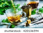 Small photo of Cup of hot tea cane sugar dry tea leaves and mint herb.