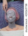 Small photo of Girl doing lifting with Alginate Peel-Off Powder facial Mask in Beauty salon. Cosmetic Mask.