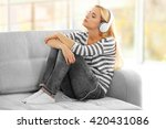 young woman on a sofa listening ... | Shutterstock . vector #420431086