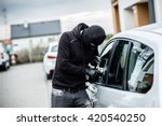 Car thief trying to break into a car with a screwdriver. Car thief, car theft. - stock photo