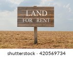 Small photo of Land for rent - wood board with text on soil background