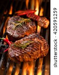 beef steaks on the grill with... | Shutterstock . vector #420591259