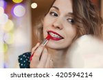 Small photo of Portrait of Beautiful happy female with brace coloring her lips with red lipstick